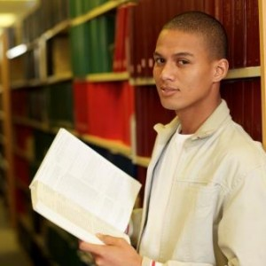 Student reading book between shelves in library, portrait