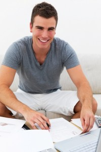 Smiling man sitting on couch and using laptop